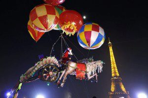 Санта-Клаус в карете из пробкового дерева подвешен на воздушных шарах недалеко от Эйфелевой башни в Париже. Инсталляция художника Насера Воланта. (Photo by Charles Platiau/Reuters)