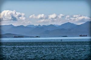 На расстоянии примерно 15 км от берега виднеются два судна с погруженными на них атомными подлодками и между ними две боевые АПЛ из-за которых Авачинская бухта в течении недели несколько раз закрывалась для передвижения всех морских судов.